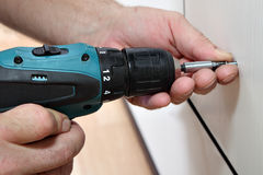 Cordless Screwdriver in the hands of joiner, close-up, screwing Stock Photos