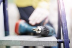 The cordless screwdriver lies on the stepladder, on a blurred ba Stock Images