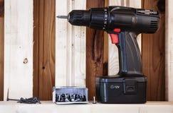 Cordless screwdriver and screws. Boards, screws and black cordless screwdriver Stock Photo