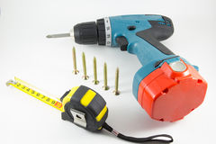 Cordless screwdriver, screws and tape measure on a white backgro Stock Photos