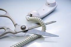 Cordón de teléfono que es cortado por las tijeras Imagenes de archivo
