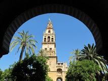 Cordoba Cathedral Arch Framed. The Cordoba Cathedral bell tower with Espana flag flying above as seen through one of the archways. Originally a Visigothic Royalty Free Stock Photo