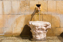 Cordoba - little fountain and capital of anicent column. Royalty Free Stock Images
