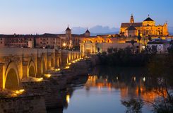 Cordoba with Roman bridge and  Mosque-cathedral in evening Stock Images