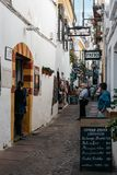 Old typical street in the jewry of Cordoba. Cordoba, Spain - April 10, 2017: Old typical street in the jewry of Cordoba with restaurants and white walls Royalty Free Stock Photos