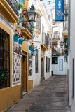 Old typical street in the jewry of Cordoba. Cordoba, Spain - April 10, 2017: Old typical street in the jewry of Cordoba with restaurants and white walls Royalty Free Stock Photo