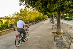 The streets of Cordoba - Spain. Cordoba/ Spain - 08/20/18 - A man biking along the river in the old town area of Cordoba - Spain royalty free stock photography