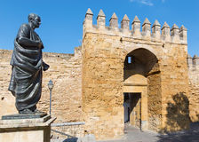 Cordoba - The statue of philosopher Lucius Annaeus Seneca the Younger by Amadeo Ruiz Olmos and medieval gate Puerta Stock Image