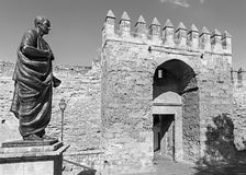 Cordoba - The statue of philosopher Lucius Annaeus Seneca the Younger by Amadeo Ruiz Olmos  and medieval gate Puerta Royalty Free Stock Images