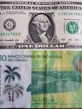 10 cordobas尼加拉瓜的钞票和美国美元钞票、背景和纹理 库存照片