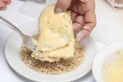 Cordon bleu panieren - Addieren des zerfallenen Crackers Lizenzfreie Stockfotos