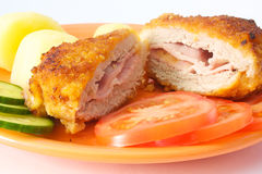 Cordon bleu with potatoes and fresh vegetables. Cordon bleu served on orange plate with potatoes and fresh vegetable and cuted in the middle Stock Photography