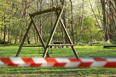 cordoned off playground with children's swing, surroundet by trees, forcus on background, blurred barrier tape