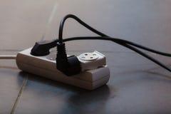 Cordones eléctricos conectados con el zócalo de poder Fotografía de archivo libre de regalías