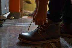 Cordones tiding modelo de sus botas marrones del color fotos de archivo libres de regalías