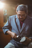 Cordonnier faisant une chaussure avec le marteau Photographie stock libre de droits