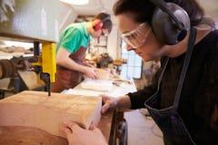 Cordonniers coupant et formant le bois pour faire des bouts de chaussure Photo stock