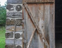 Cordwood and log beams with an old wooden door at Old World Wisconsin royalty free stock images
