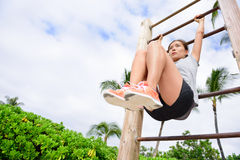 Core cross training fit woman doing abs exercises. On beach on fitness vertical ladder rack. Young active athlete working out abs muscles outside royalty free stock images