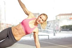 Core exercise. Young beautiful woman doing core exercise outdoor royalty free stock photos