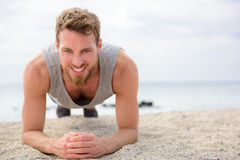 Core exercise - fitness man doing plank outside. Crossfit training fitness man doing plank core exercise working out his midsection muscles. Fit athlete fitness stock image