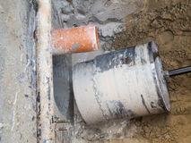Core Hole Drilling. Look at a finished core hole hole with bit and core in a raised ditch in front of a concrete wall Royalty Free Stock Image