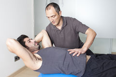 Core stability. Physical therapist with patient in a gym Stock Photo