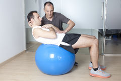 Core stability. Physical therapist with patient in a gym Stock Photography