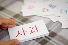 Coreano; Aprendizaje de la nueva palabra con las tarjetas del alfabeto; Escritura de A imagen de archivo
