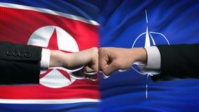 Coreia do Norte contra o conflito da OTAN, relações internacionais, punhos no fundo da bandeira vídeos de arquivo