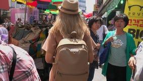 Coreia do Sul - 29 de maio de 2018: viajante fêmea caucasiano que anda no mercado de rua asiático de seoul filme