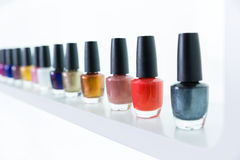 Cores coloridas do verniz para as unhas em seguido no bar dos pregos no branco Foto de Stock Royalty Free