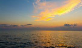 Cores do nascer do sol do por do sol a nuvem na laranja sobre a superfície do mar Imagens de Stock