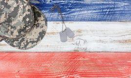 Cores nacionais dos EUA com tampão militar e etiquetas da identificação no plano de madeira Fotografia de Stock