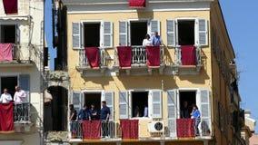 CORFÚ, GRECIA - 7 DE ABRIL DE 2018: Potes de arcilla del tiro de Corfians de ventanas y balcones el sábado santo para celebrar la metrajes