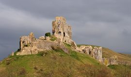 Corfe Castle. Dramatic Corfe Castle Ruin bathed in sunlight as storm clouds gather Royalty Free Stock Photo