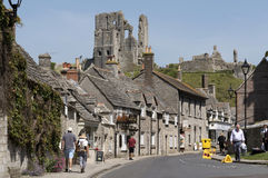Corfe Castle famous ruins above the town in Dorset UK. Quaint street in Corfe Castle Dorset England UK overlooked by the castle ruins Royalty Free Stock Photos