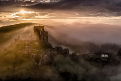 Corfe castle on a misty morning in Dorset. The iconic Corfe castle in Dorset on a misty morning at sunrise stock photo