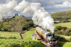 Corfe Castle. Steam locomotive heading towards swanage, passing by the famous and iconic Corfe Castle Royalty Free Stock Photography