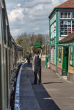 CORFE CASTLE, UK - APRIL 13, 2016: English railways guard waves. His flag to signal stream train departure Stock Images