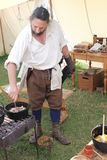 CORFE, DORSET,ENGLAND - AUGUST 06, 2015: A mediaeval re-enactor stirs an Old English recipe of pork andapple. CORFE, DORSET,ENGLAND - AUGUST 06, 2015: A Stock Photography
