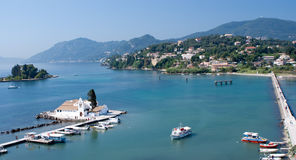 Corfu. Scenic bay at Corfu, dock out to a white-washed church surrounded by town and hills Royalty Free Stock Image