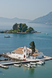 Corfu. Scenic bay at Corfu, dock out to a white-washed church surrounded by town and hills Stock Photos