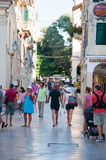 CORFU-AUGUST 27: Kerkyra shadow street in the old town, tourists go shopping on August 27, 2014 on Corfu island, Greece. Royalty Free Stock Image