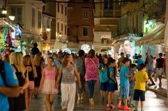 CORFU-AUGUST 25: Kerkyra upptagen gata på natten med folkmassan av folk på Augusti 25, 2014 i den Kerkyra staden på den Korfu ön, Arkivbilder