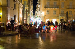 CORFU-AUGUST 25: Tourists have dinner in a local restaurant at night on August 25, 2014 in Kerkyra town on Corfu island, Greece. Royalty Free Stock Image