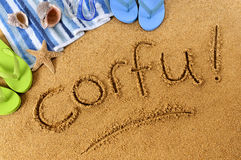 Corfu beach sand word writing. The word Corfu written on a sandy beach, with beach towel, starfish and flip flops Royalty Free Stock Photos