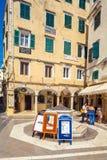 CORFU, GRÉCIA - 1º DE JULHO DE 2011: Os turistas estão o pi próximo da propaganda Imagem de Stock Royalty Free