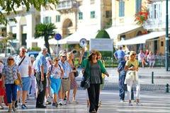 CORFU, GRECJA, 18 2018, turyści bierze wycieczkę turysyczną miasto towarzyszący przewdonikiem obrazy royalty free