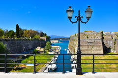 Corfu old fortress city walls. The old fortress in Corfu Town, with water canal and boats docked in the sun Stock Photos